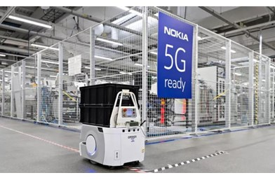 Nokia factory with robot and 5G banner on cage