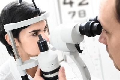 Optometrist performing eye exam on female patient