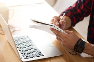 Man using laptop and notepad