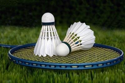 Two shuttlecocks sit atop a badminton racquet