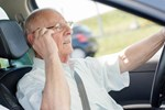 Older man wearing glasses driving