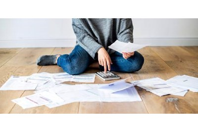 Woman on the floor surrounded by paperwork