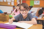 Child wearing glasses smiles in a classroom