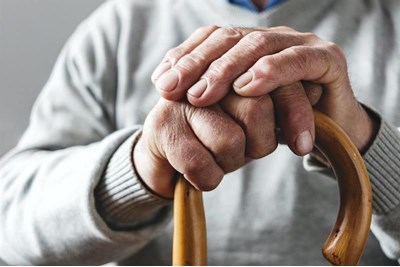 Elderly person holding a walking stick