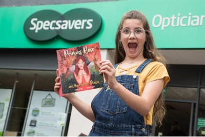 Lowri Moore holding her book outside Specsavers