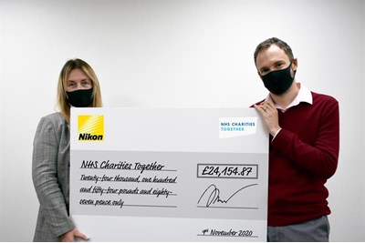 Nikon staff holding a cheque