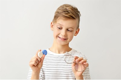 Child holding contact lens pot and frames