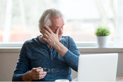 Person rubbing eyes at a computer